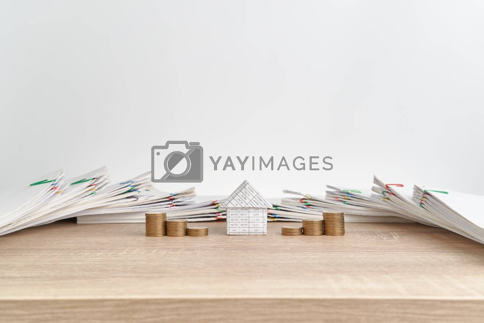 Royalty free image of House between step pile of gold coins on wooden table by eaglesky