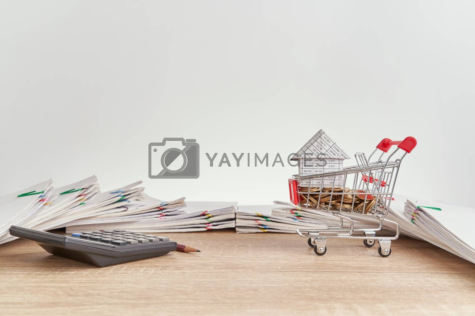 Royalty free image of House gold coins in shopping cart and calculator with pencil by eaglesky