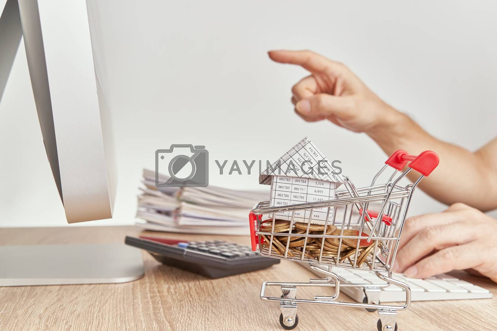 Royalty free image of House gold coins in shopping cart have blur pointing finger by eaglesky