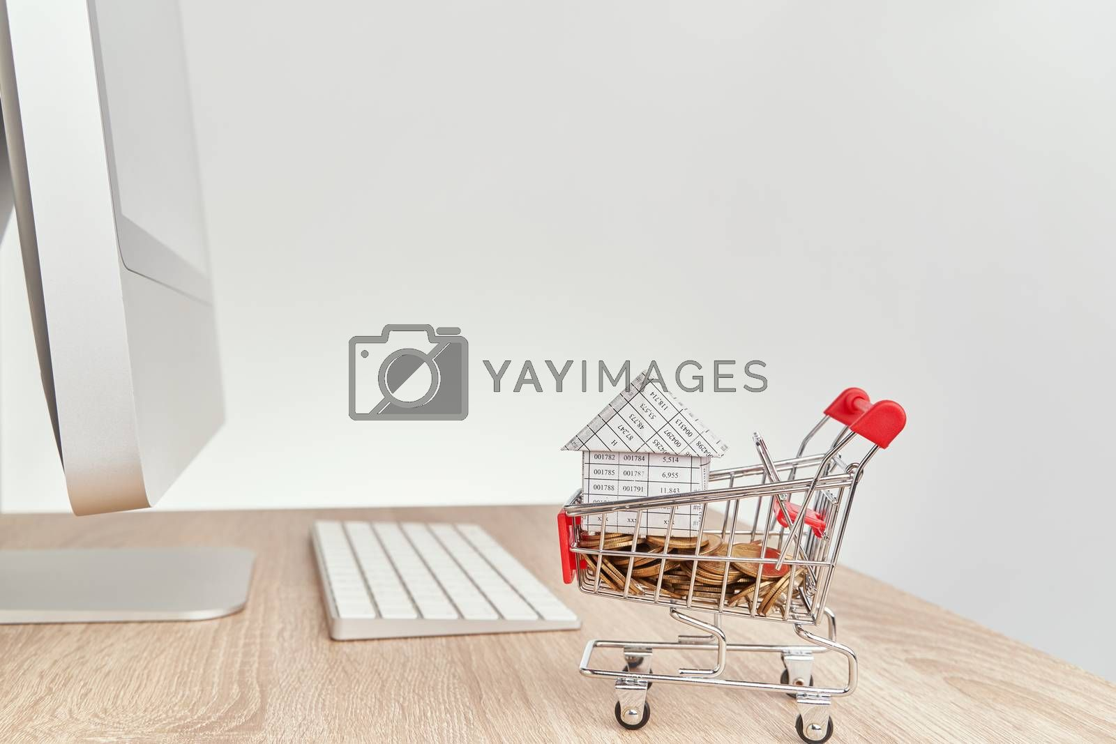 Royalty free image of House gold coins in shopping cart on wooden computer table by eaglesky
