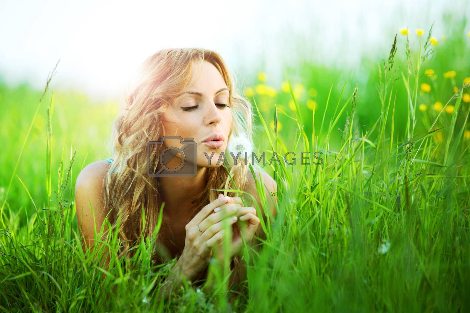 Blonde girl lays on spring meadow and blow on dandelion i wish concept