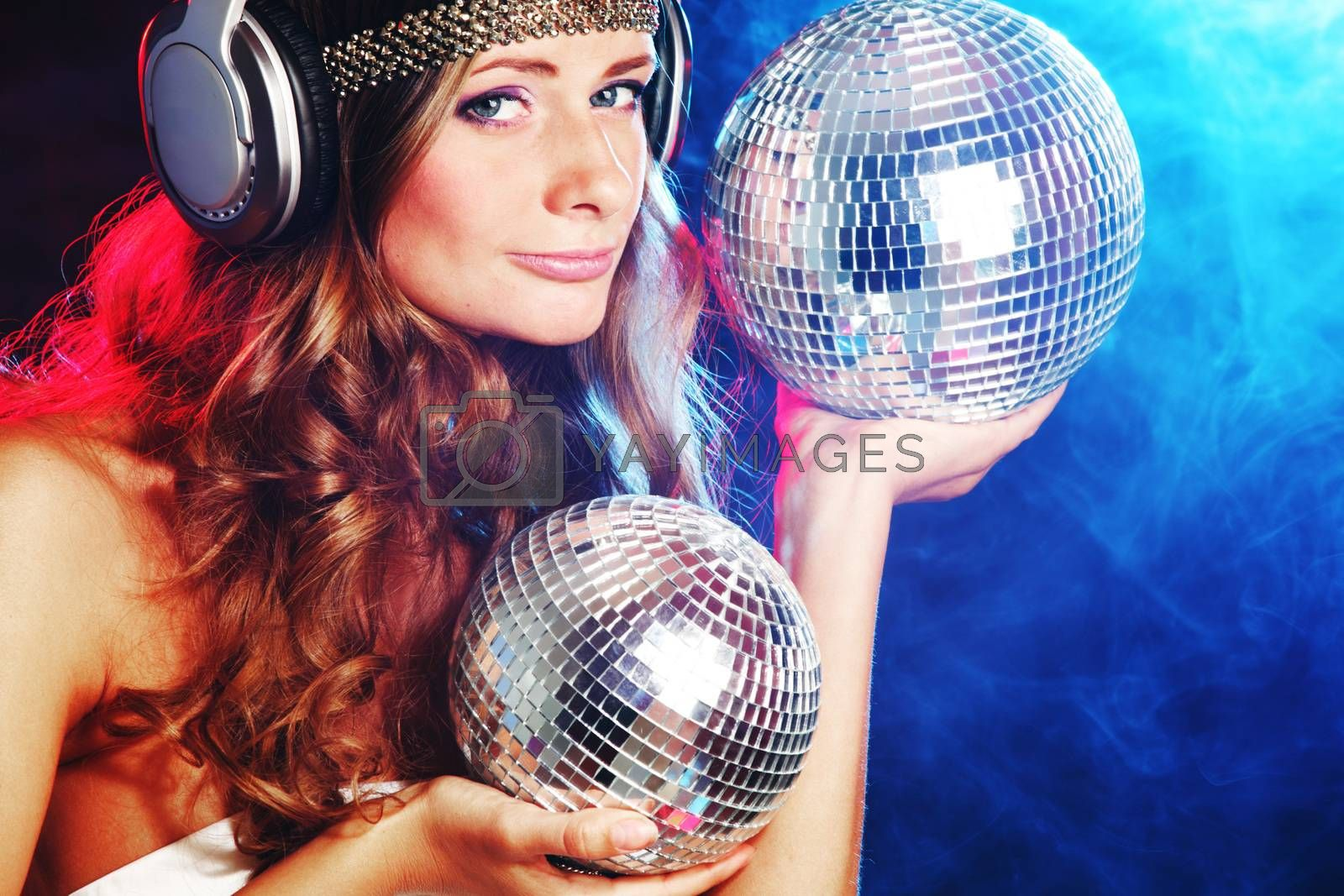 Disco girl enjoys music in head phones holding mirror disco ball over black and colorful smoke background