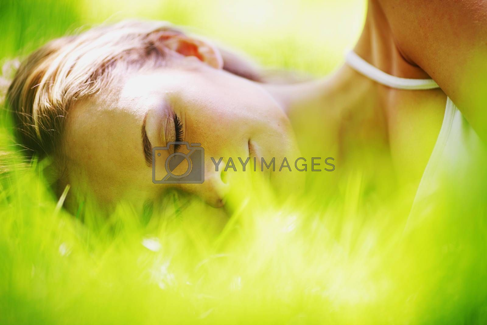Beautiful young woman sleep on green spring grass