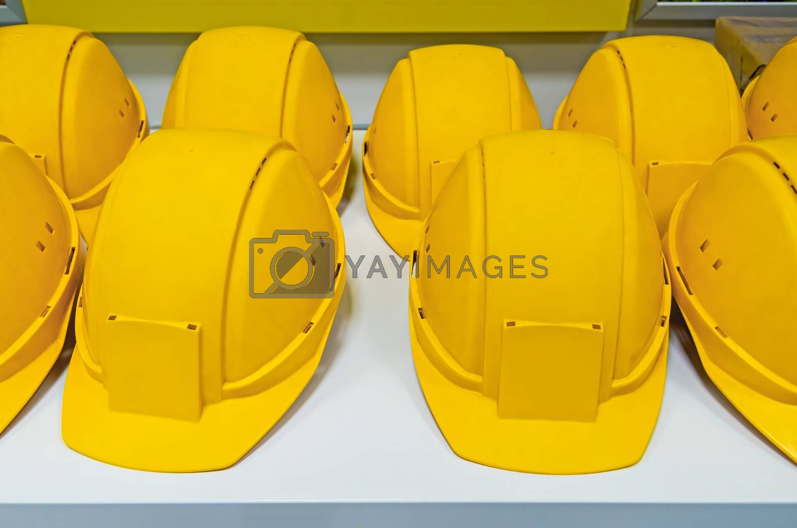 Yellow protecting hard hats on bench ready for workers to pick them.