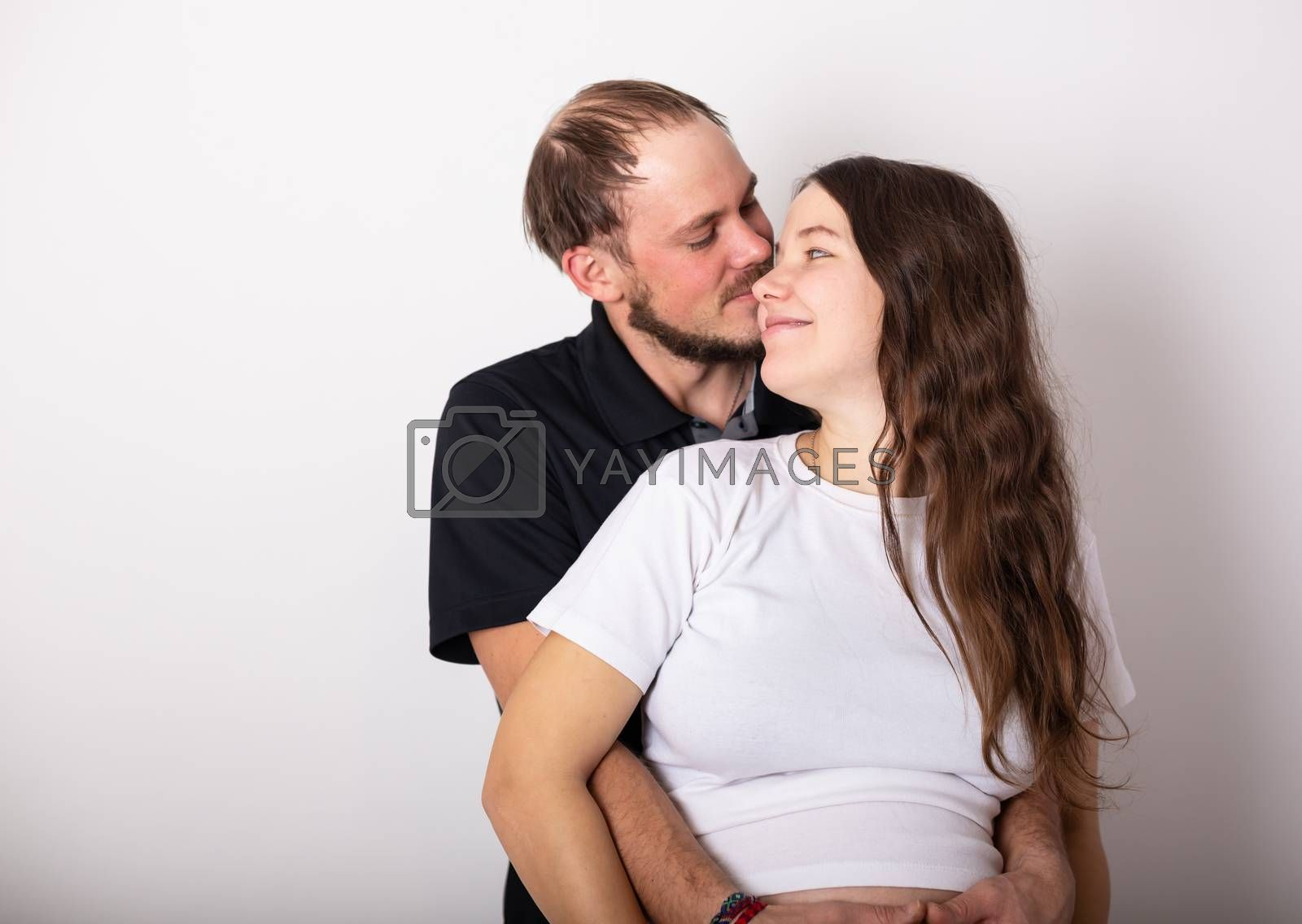 Handsome man is listening to his beautiful pregnant wife's tummy and smiling.