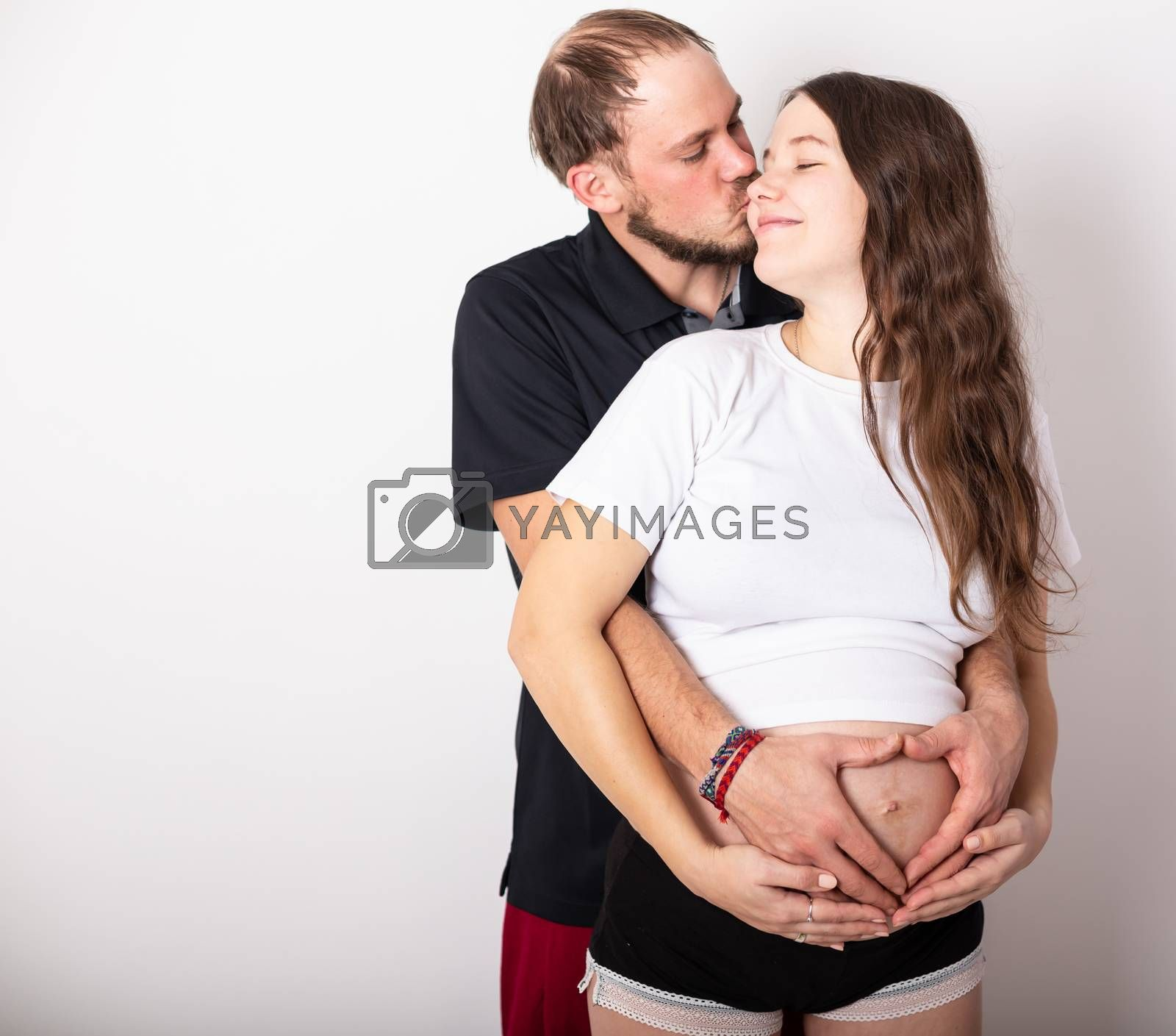 Cropped image of beautiful pregnant woman and her handsome husband hugging the tummy.