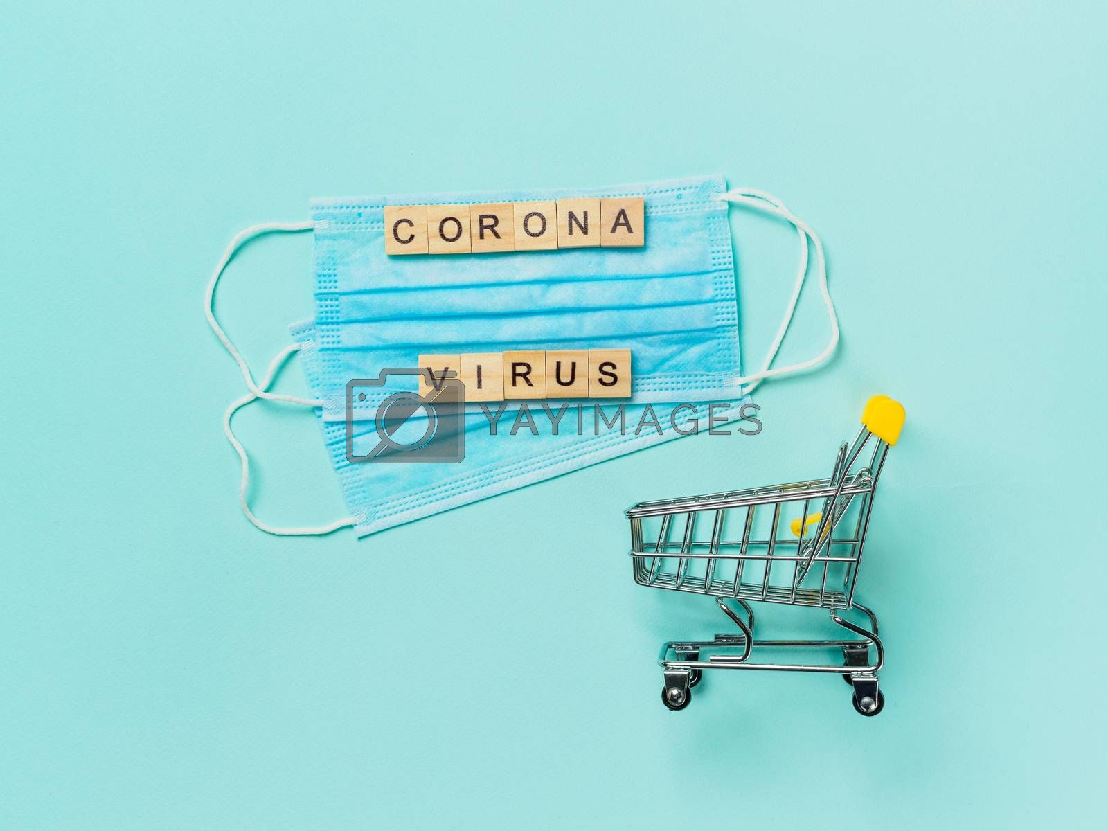 Coronavirus and shopping concept. Medical breathing mask and toy shopping trolley on blue background. Coronavirus concept top view. Copy space