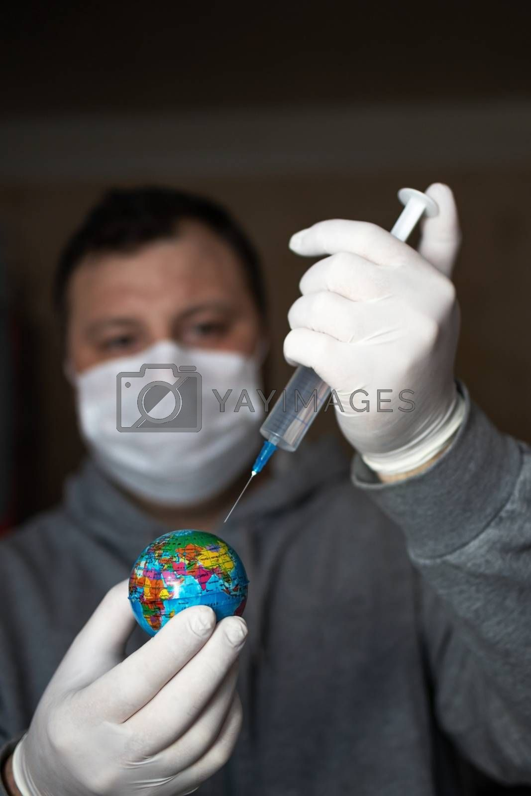 Man in medical mask and gloves making injection of coronavirus vaccine to planet earth. COVID-19 concept, global epidemic, cure for pandemic, stopping the epidemic, virus vaccine.