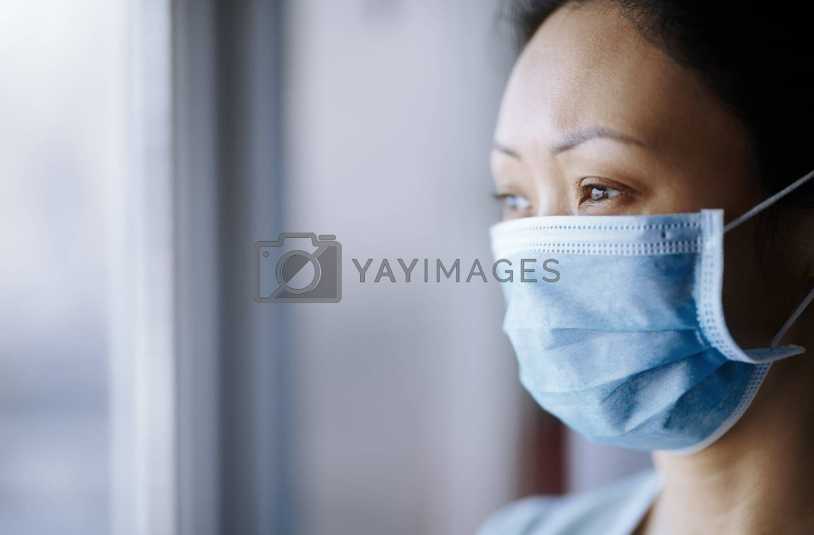 Royalty free image of Woman staying at home wearing protective surgical mask by Novic