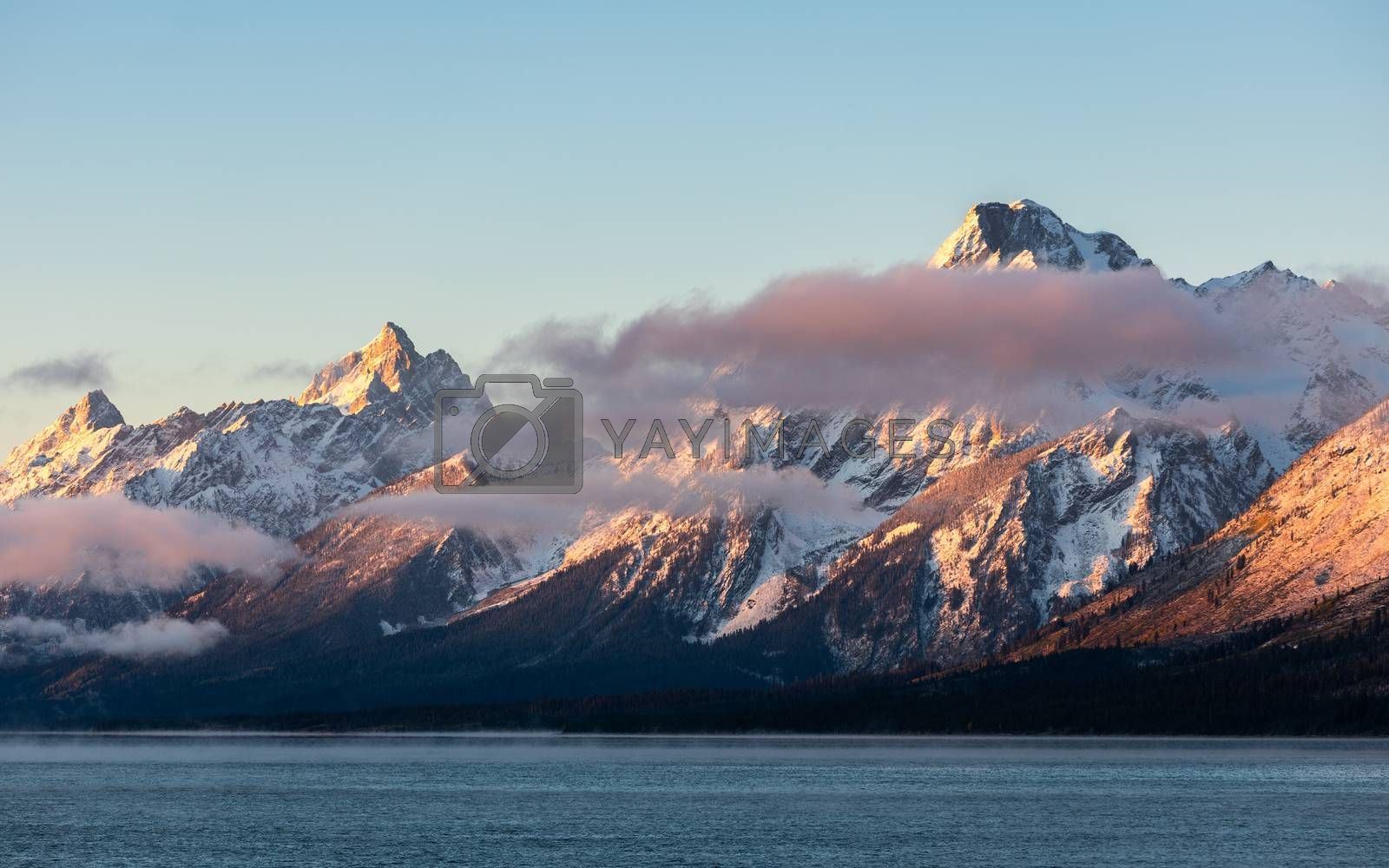 Mountain range covered by snow and cloud at sunrise of Jackson Lake, Grand Teton National Park, Wyoming, USA.