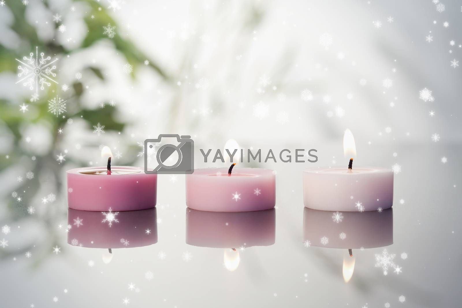 Composite image of snow falling against lighted candles on a mirror