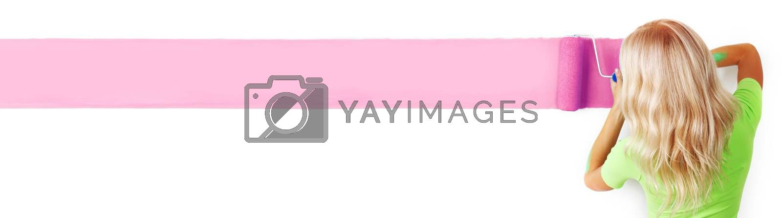 Young woman paints her appartment walls pink using paint roller , isolated on white background, copy space for text