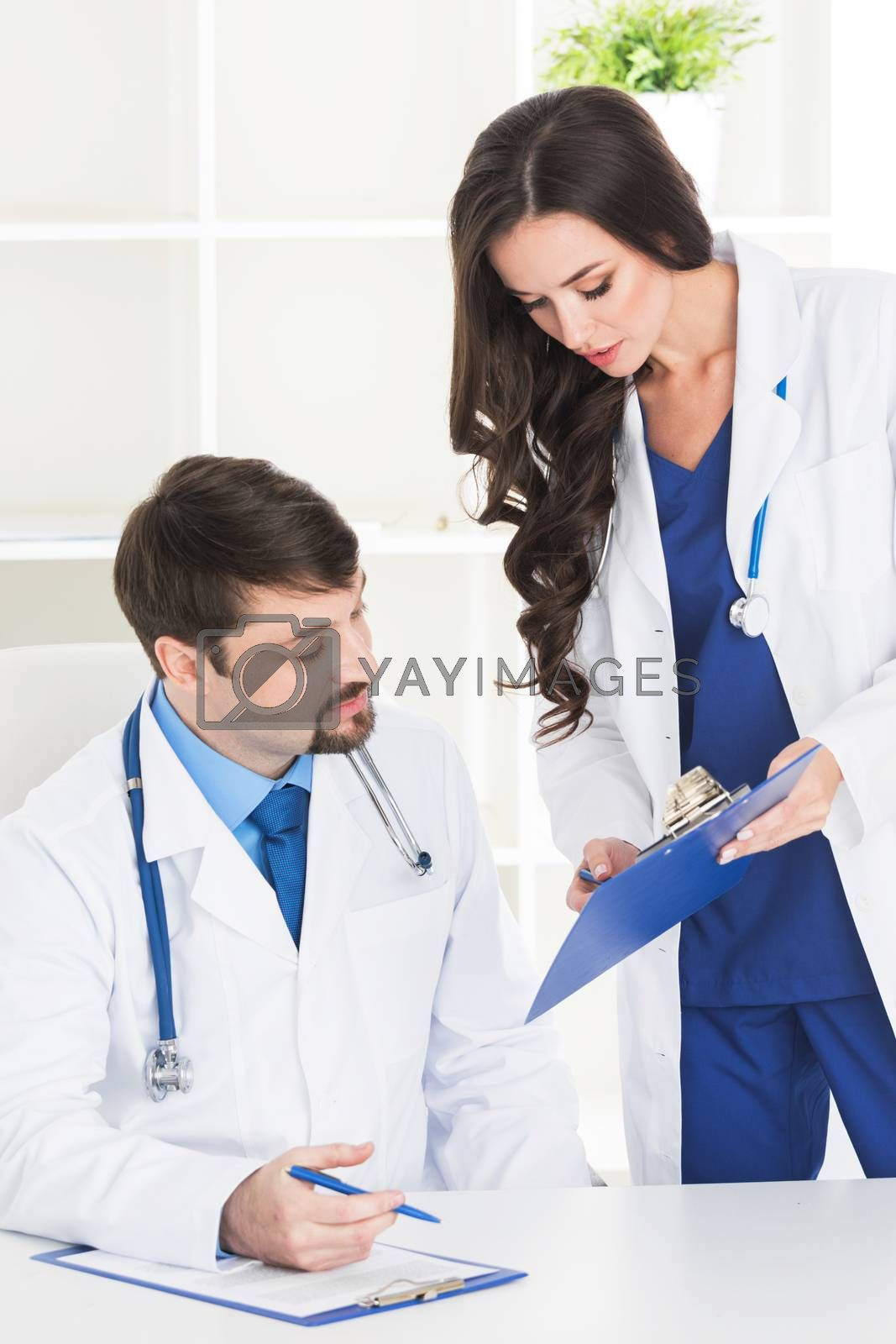 Professional medical doctor and his assistant working in the office, she is holding a clipboard and he is signing medical records