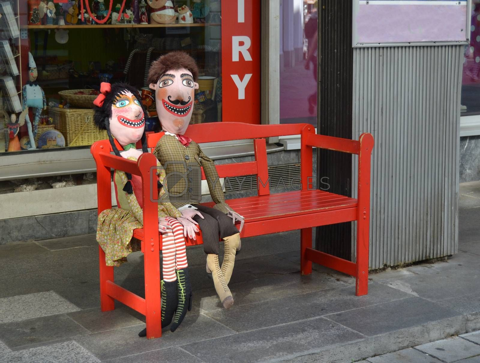 Puppet couple imitating a married couple sitting on a bench in the street