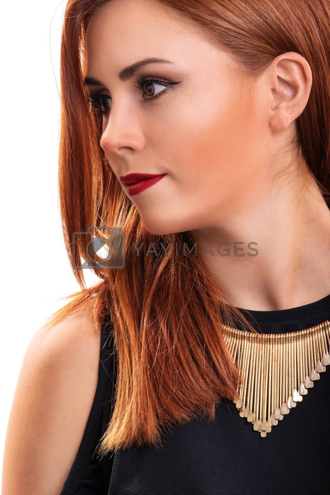 Profile shot of a beautiful, attractive redheaded young woman with clean make up, stylish black blouse and modern necklace, isolated on white background. Fashion and beauty concept.