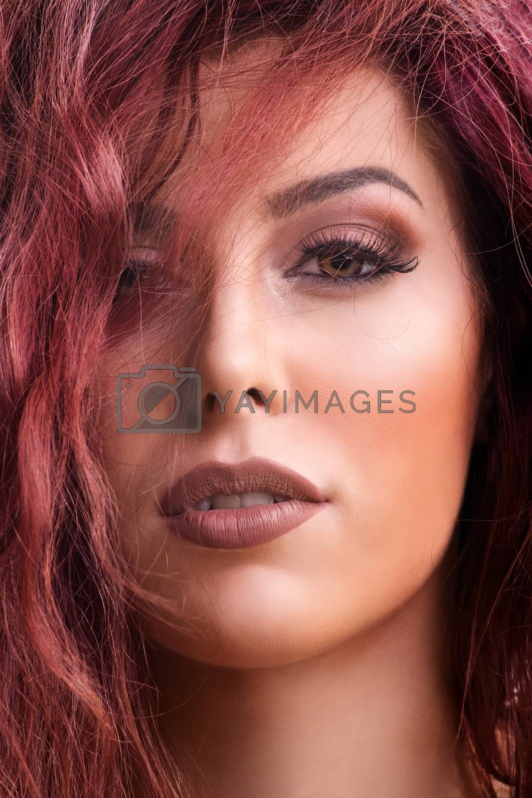 Close up portrait shot of a beautiful redhead young woman with dark smokey eye makeup and red lipstick with hair over her eye. Female fashion. Beautiful young woman with perfect skin and long hair.