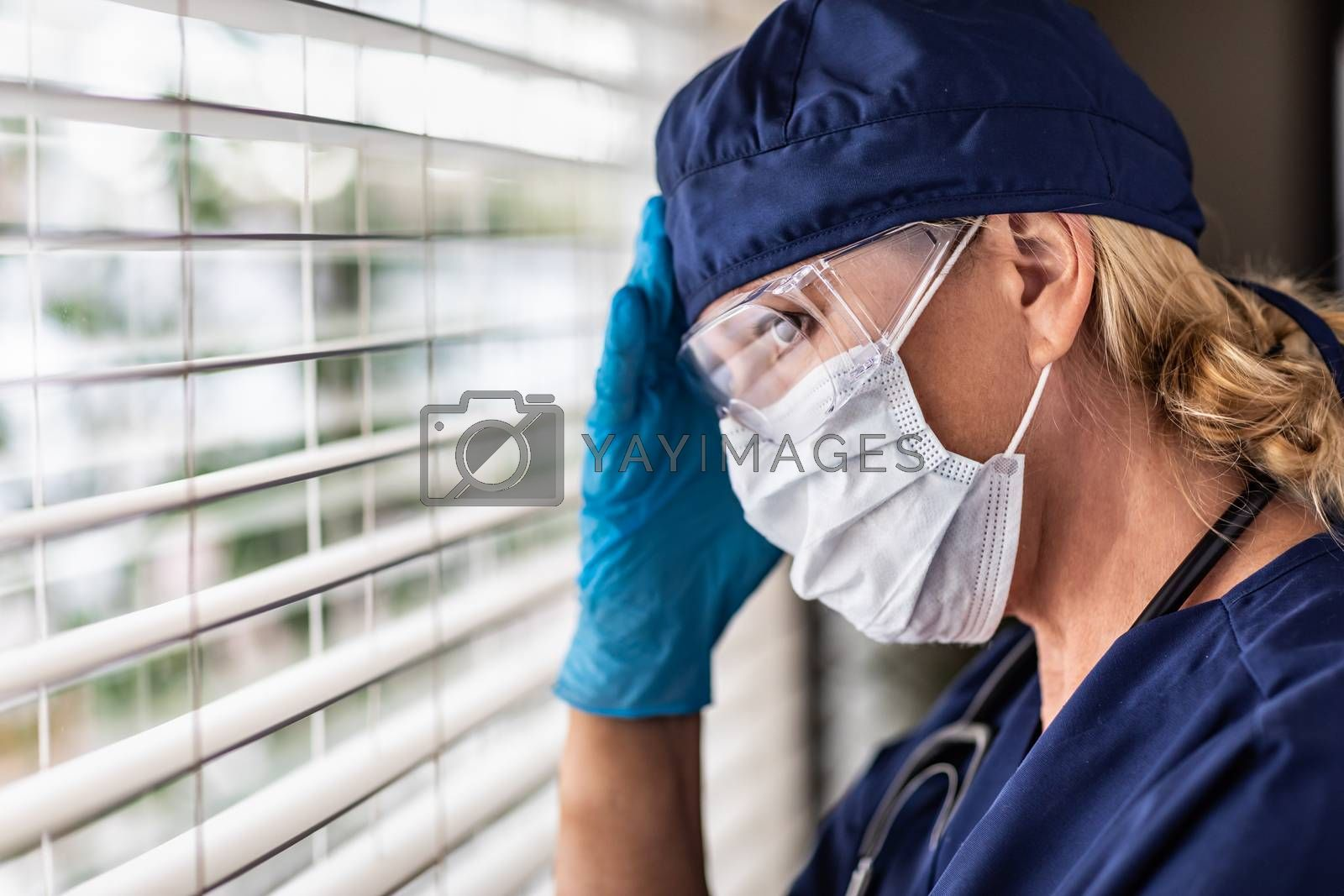 Female Doctor or Nurse On Break At Window Wearing Medical Face Mask and Goggles.