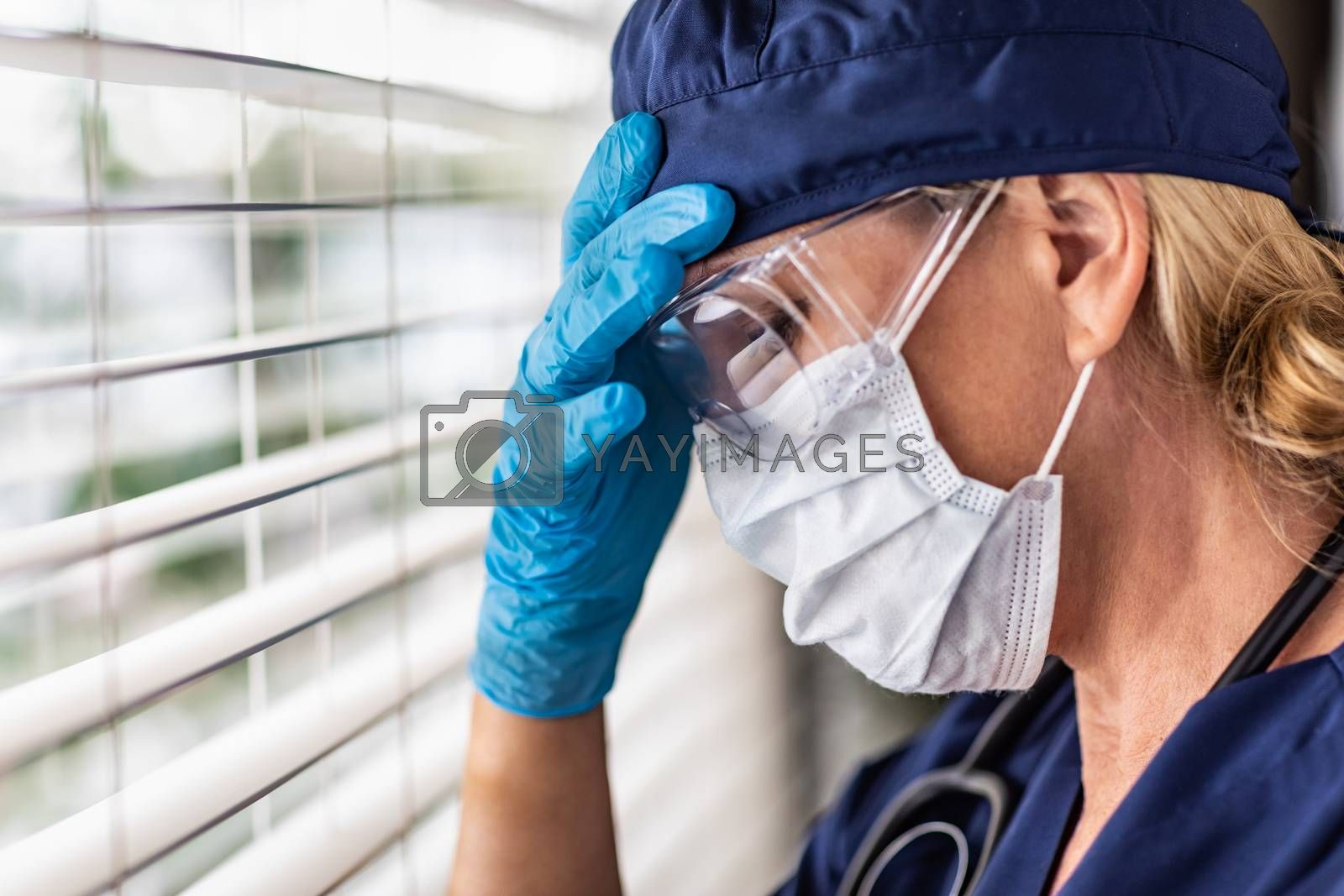 Stressed Female Doctor or Nurse On Break At Window Wearing Medical Face Mask and Goggles.