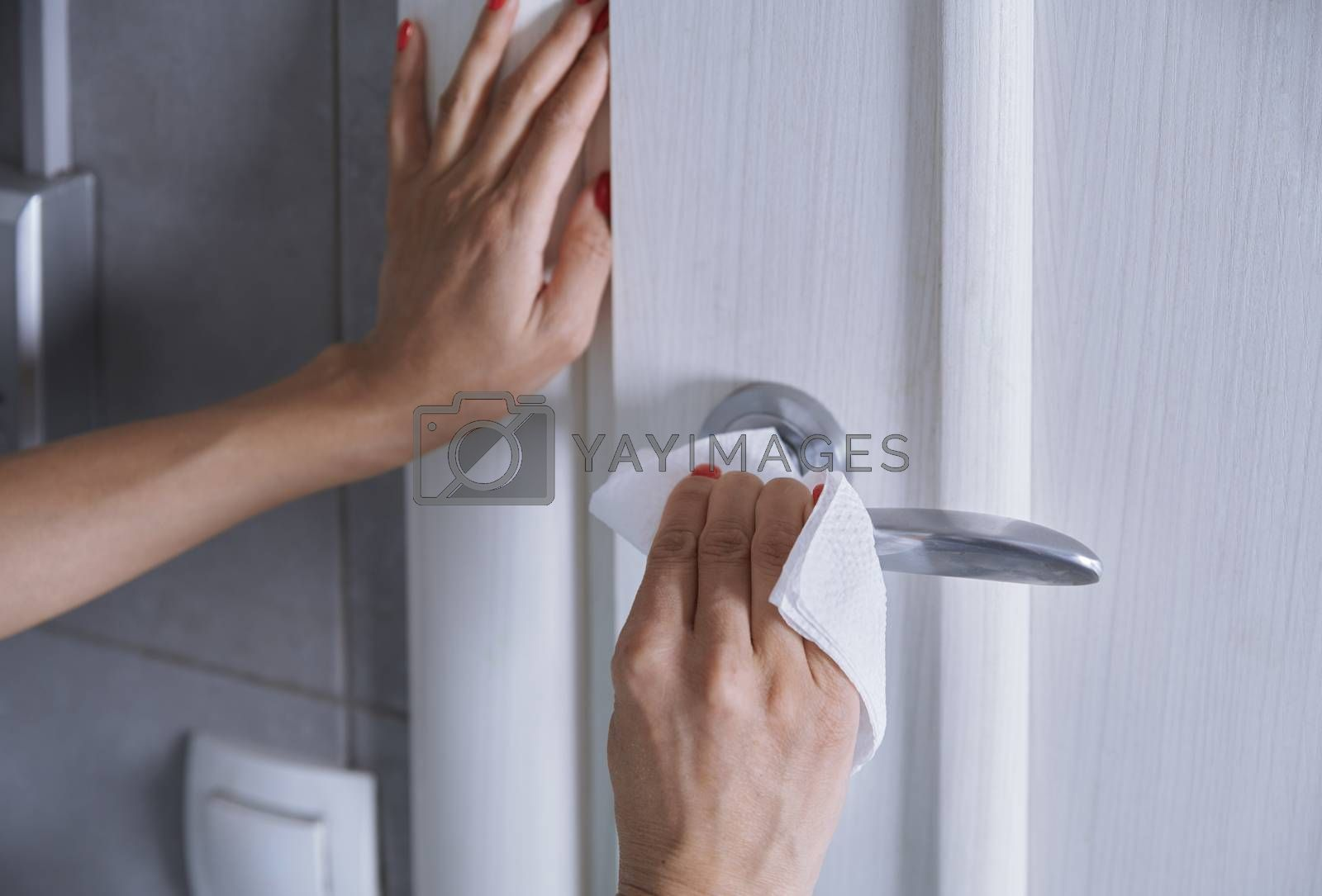 Woman cleaning the door handle with disinfecting wipe