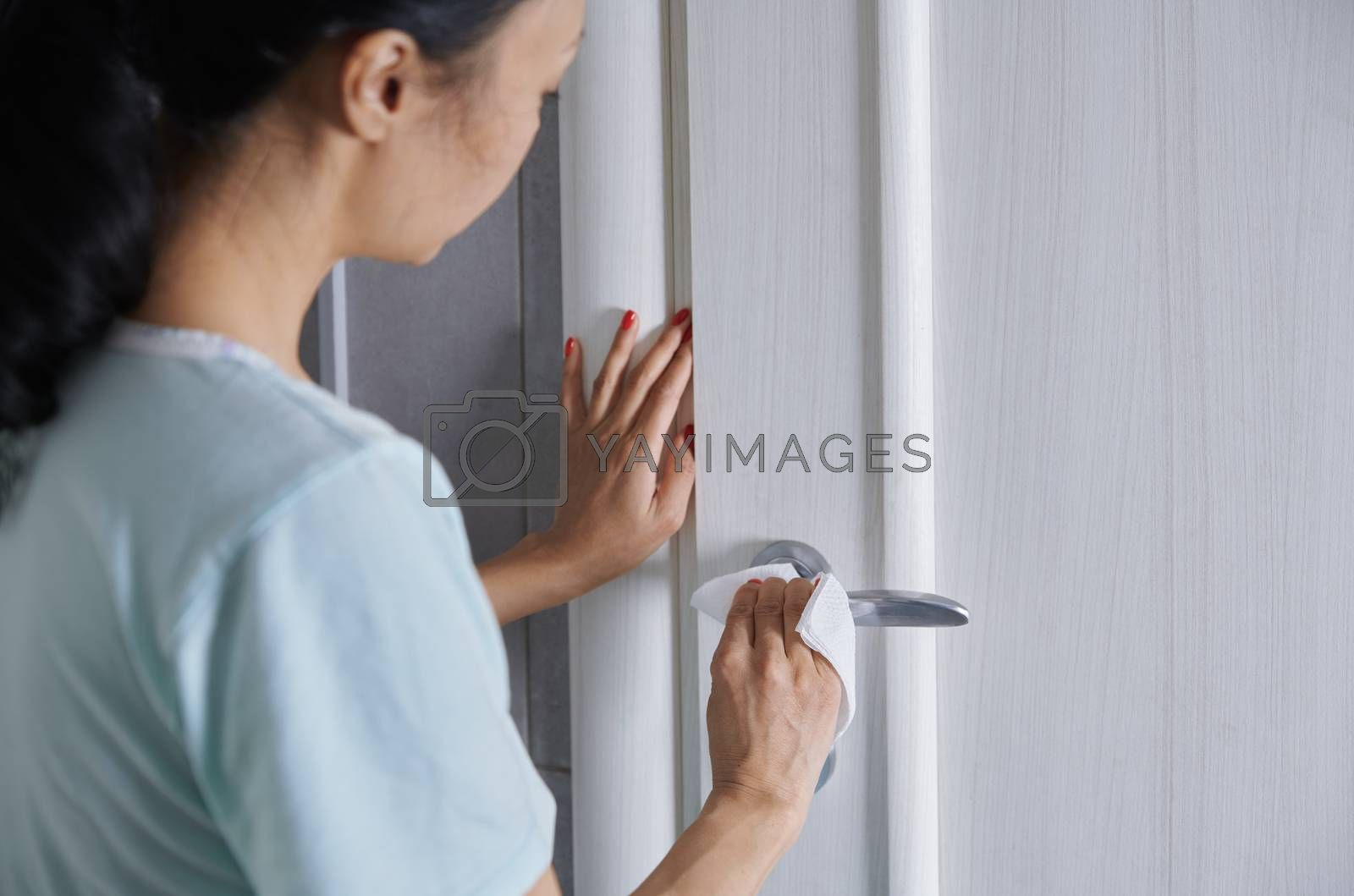 Royalty free image of Woman cleaning the door handle with disinfecting wipe by Novic