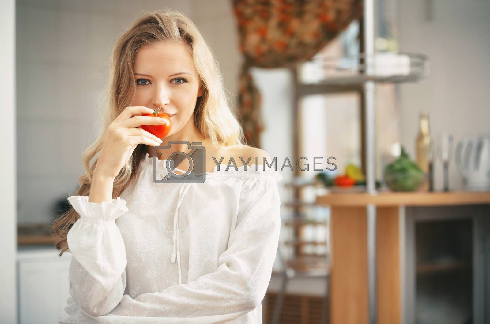 Royalty free image of Blond lady with ripe tomato at the kitchen by Novic