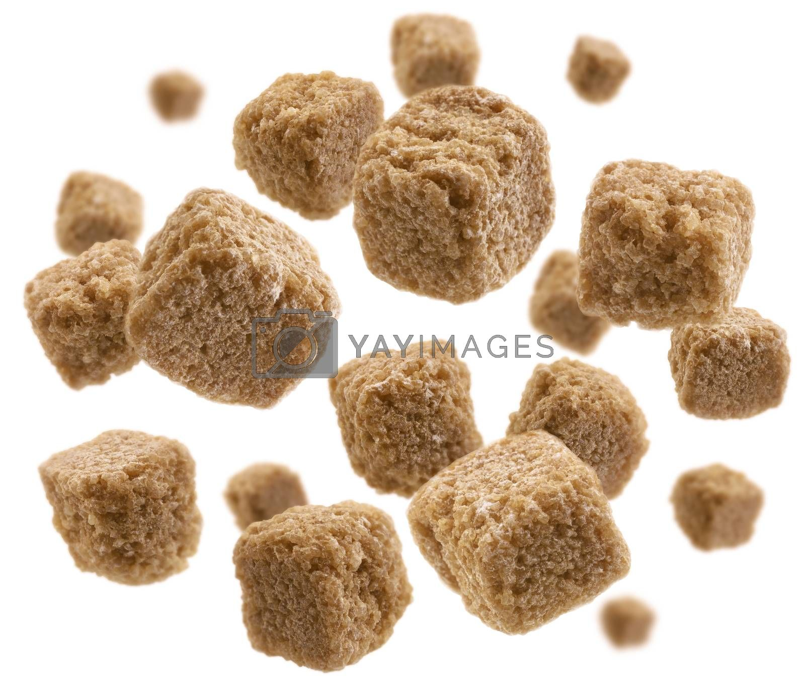 Brown cane sugar levitates on a white background.