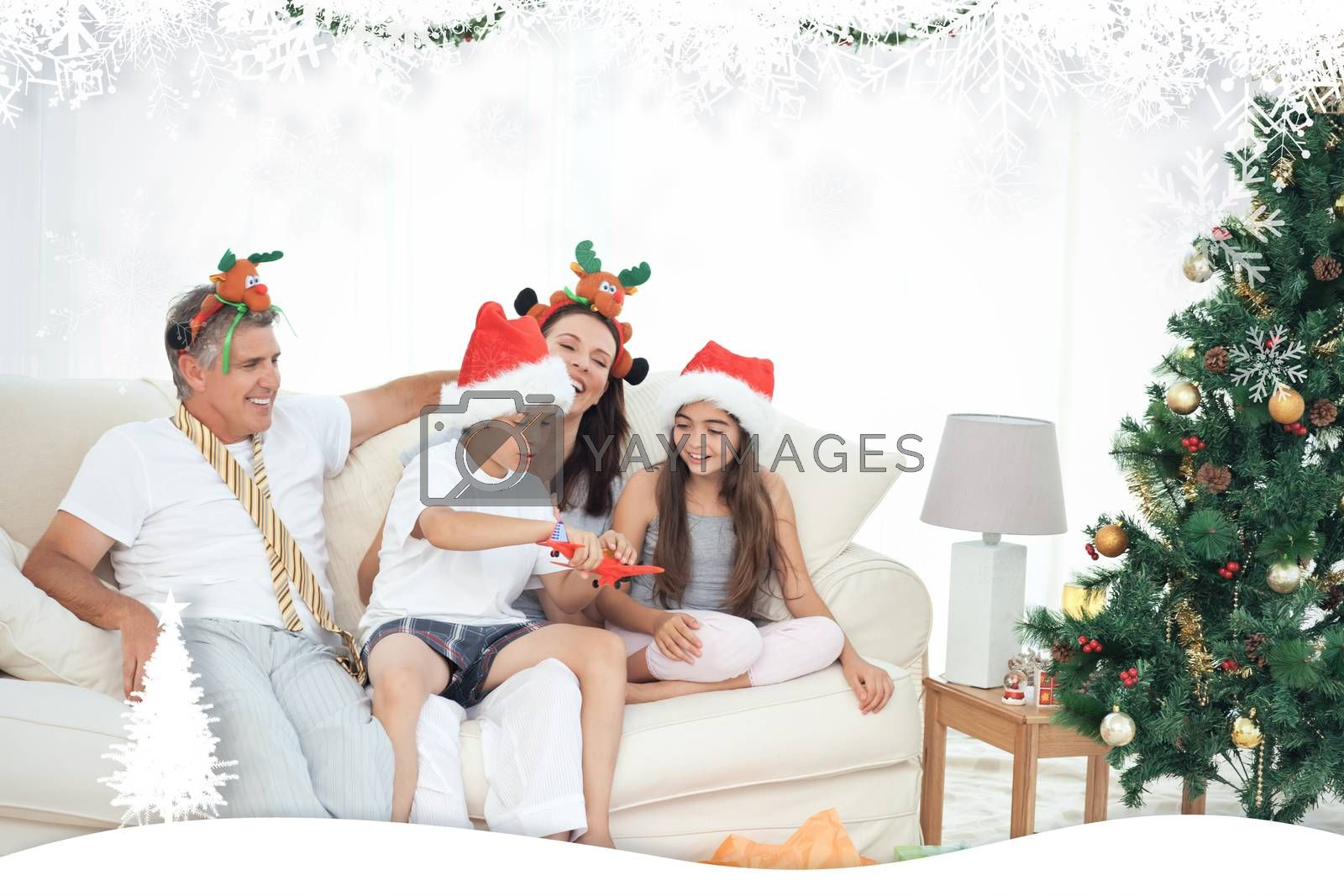 Family on Christmas day looking at their presents at home against fir tree forest and snowflakes