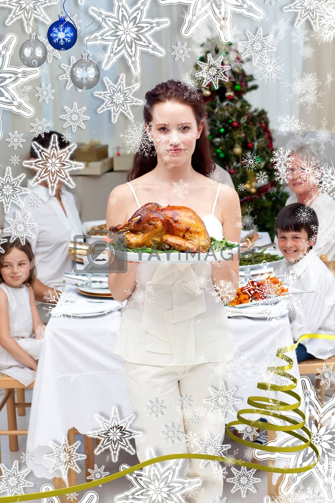 Mother showing turkey for Christmas dinner against snow falling