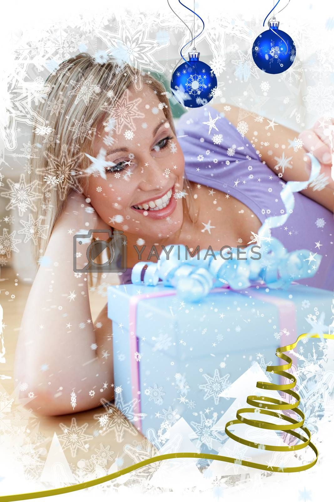 Cheerful blond woman holding a present lying on the floor against snow falling
