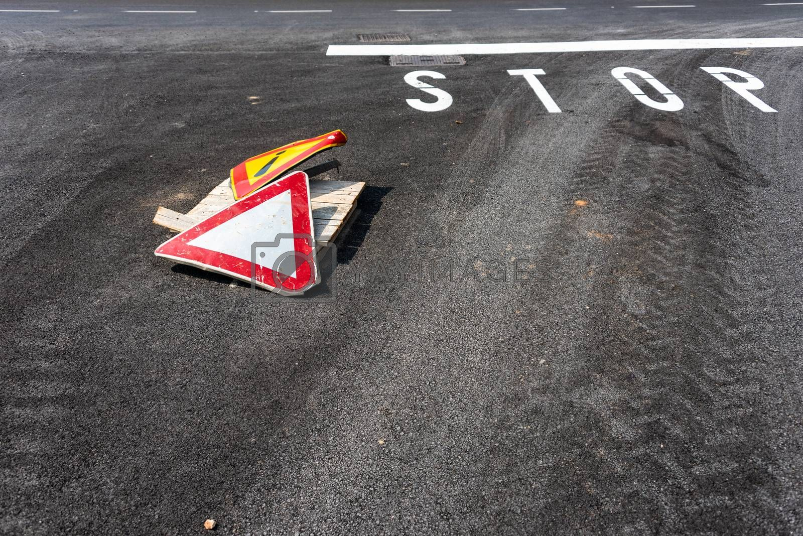 Warning sign exclamation mark in yellow triangle  and pay attention to the right of way sign on asphalt road with white stop sign