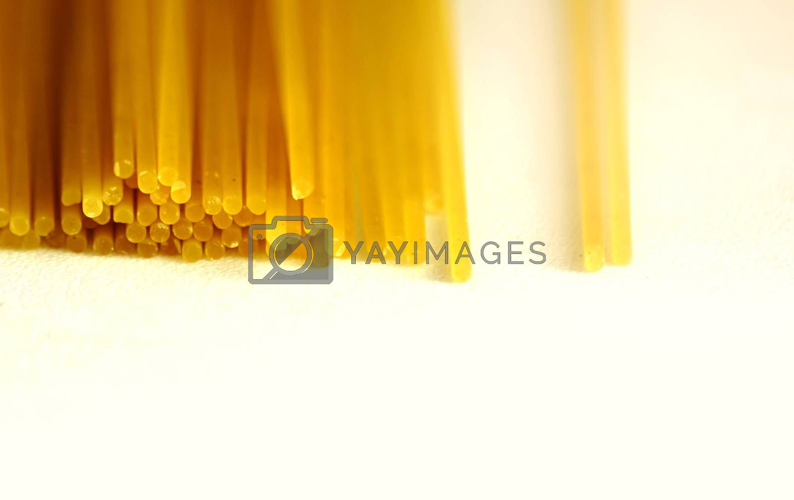 a group of raw spaghetti stacked on a white surface. Dried durum wheat pasta ready to be cooked