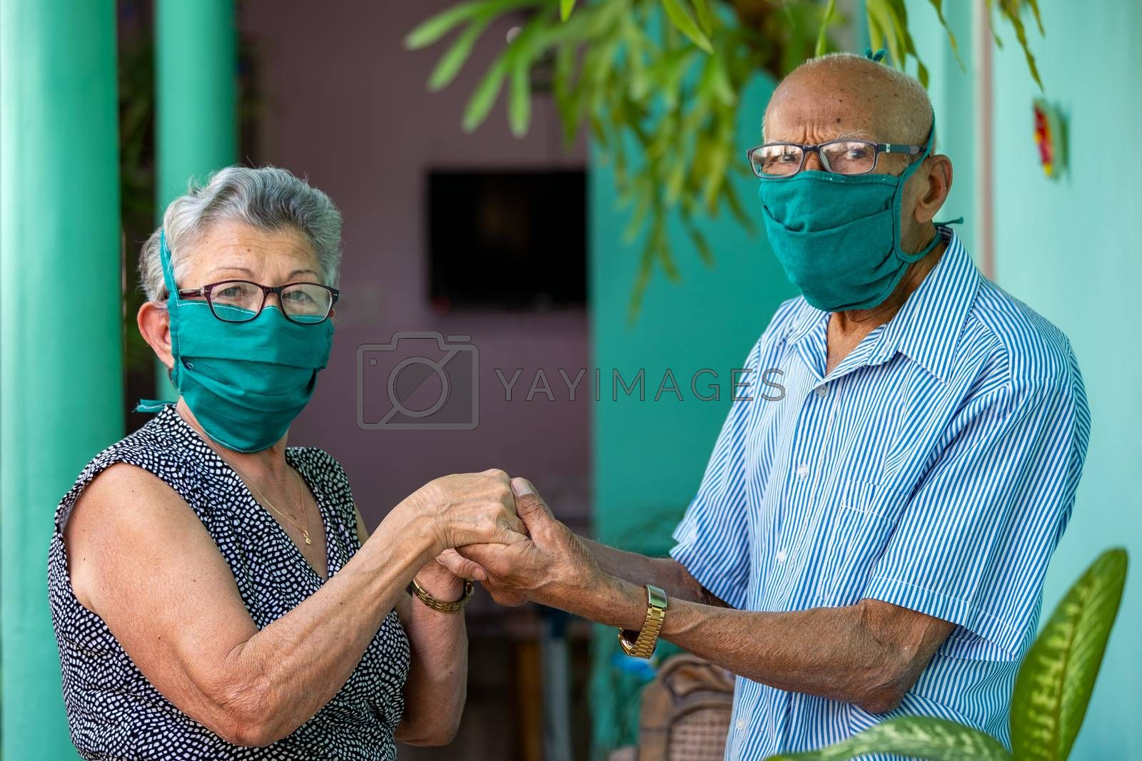 An elderly couple, both wearing face mask