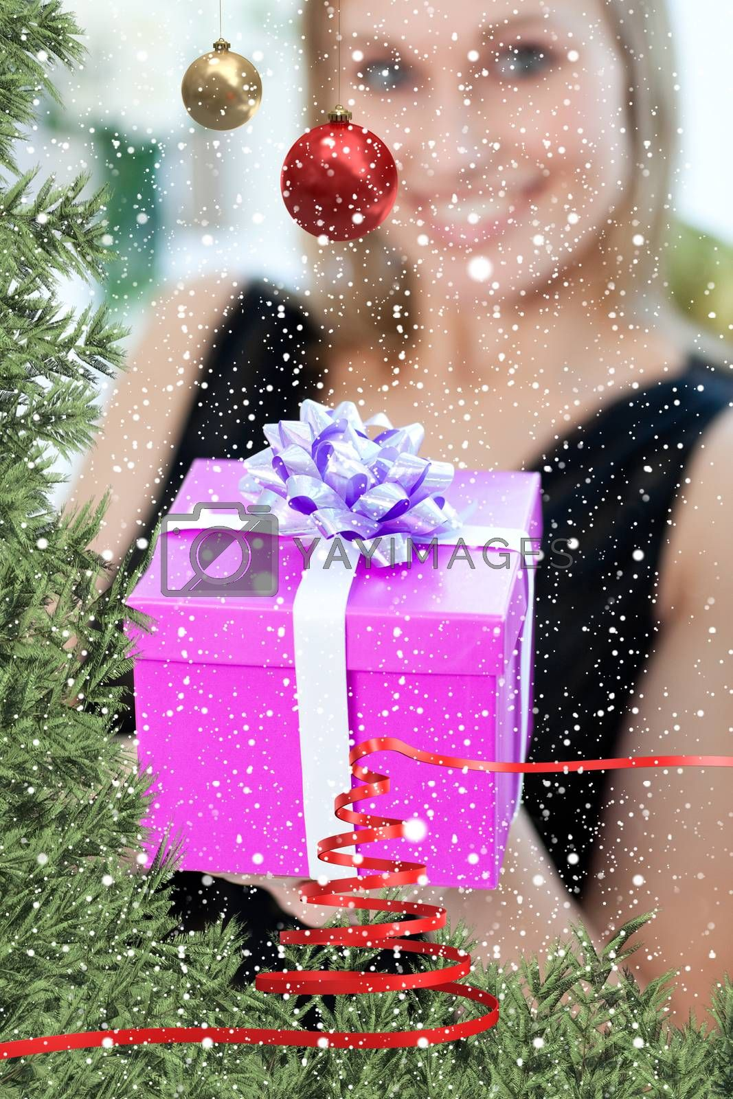 Blond woman opening a gift sitting on a sofa against snow falling