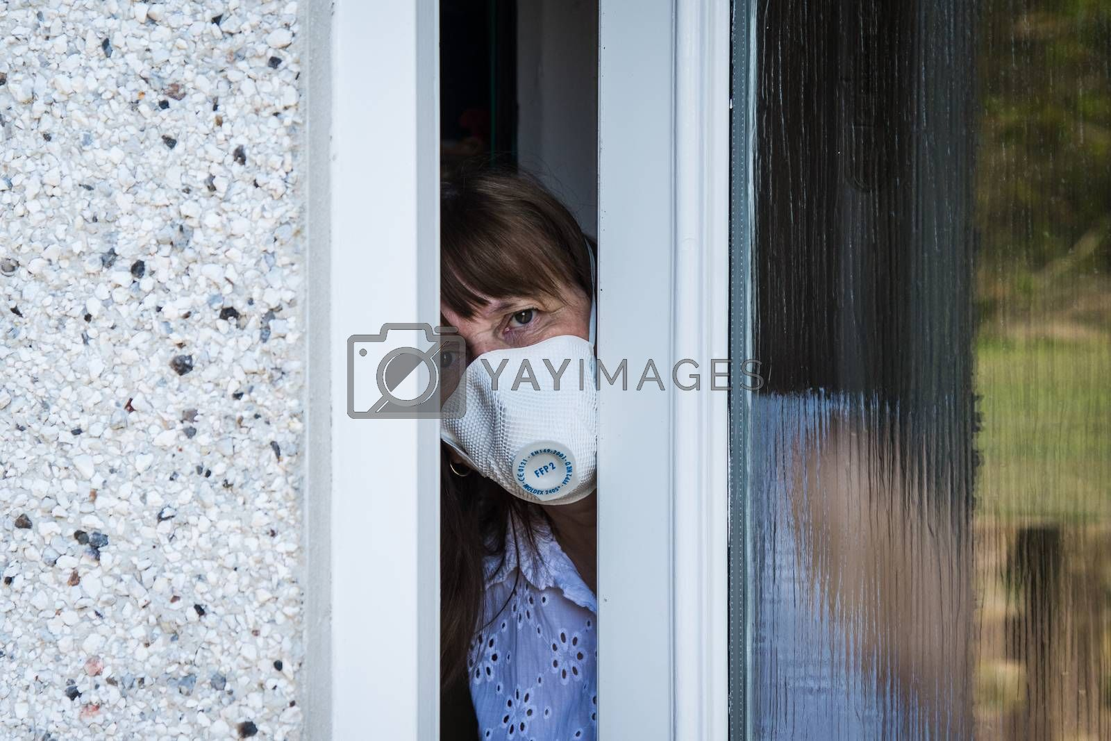 woman in a protective medical mask looking out from behind a partially open door. Coronavirus epidemic UK