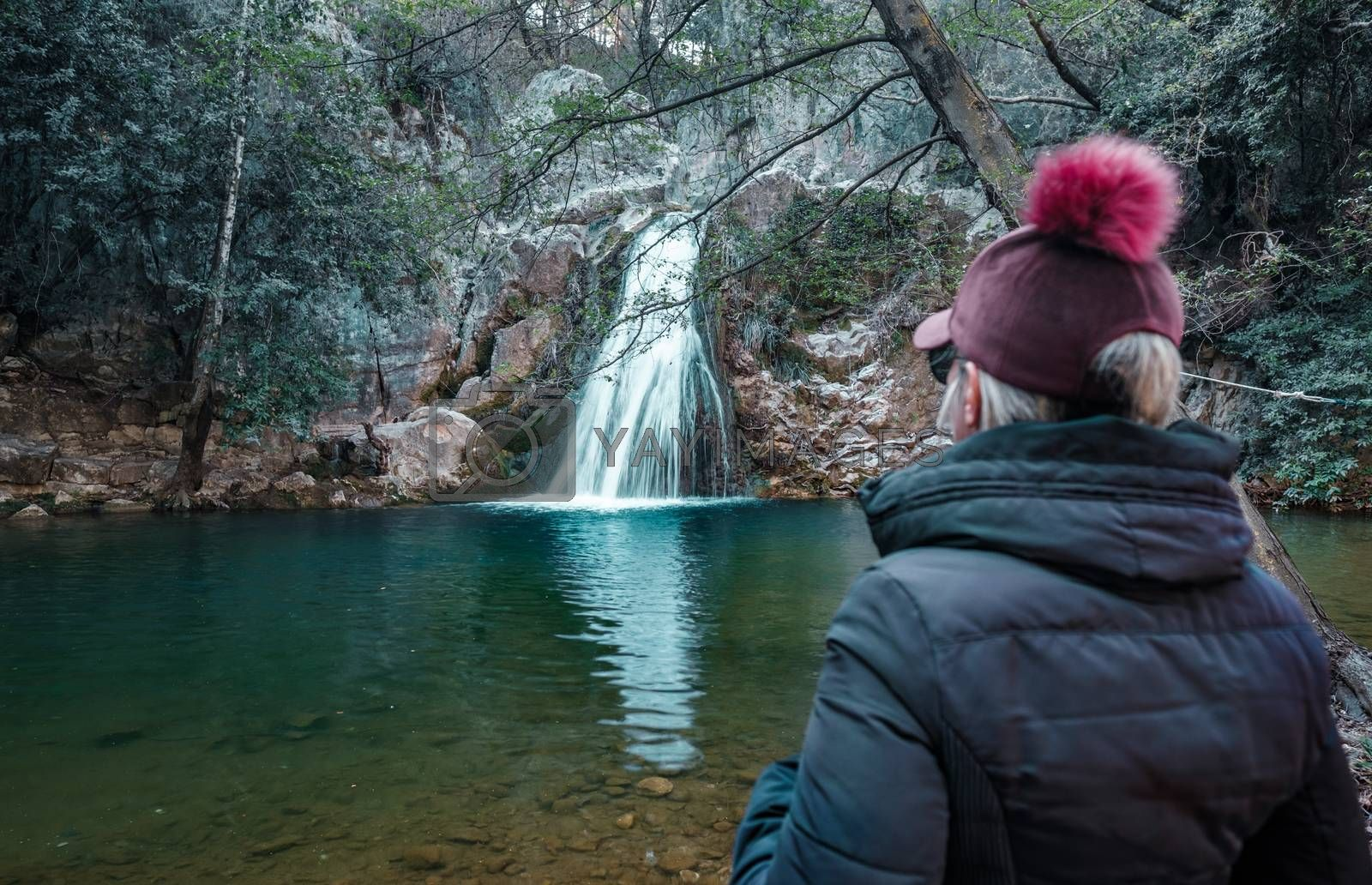 Adult woman standing in front of waterfall and enjoying the view at Kocacay Deresi, Antalya, Turkey.