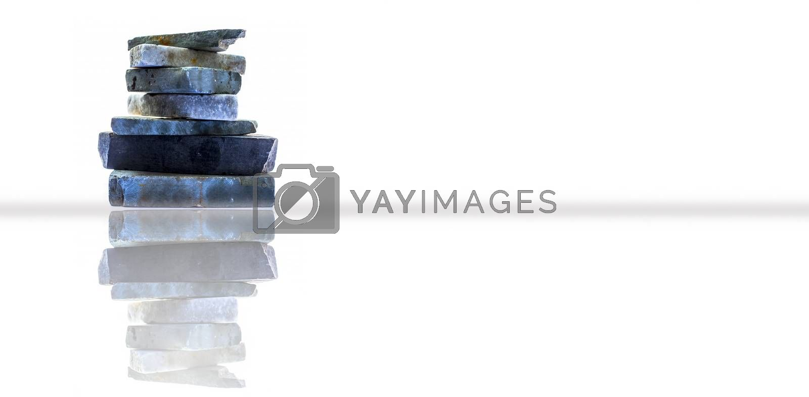 Horizontal shot of a bunch of rocks stacked on each other. Isolated on a white background along with its reflection.