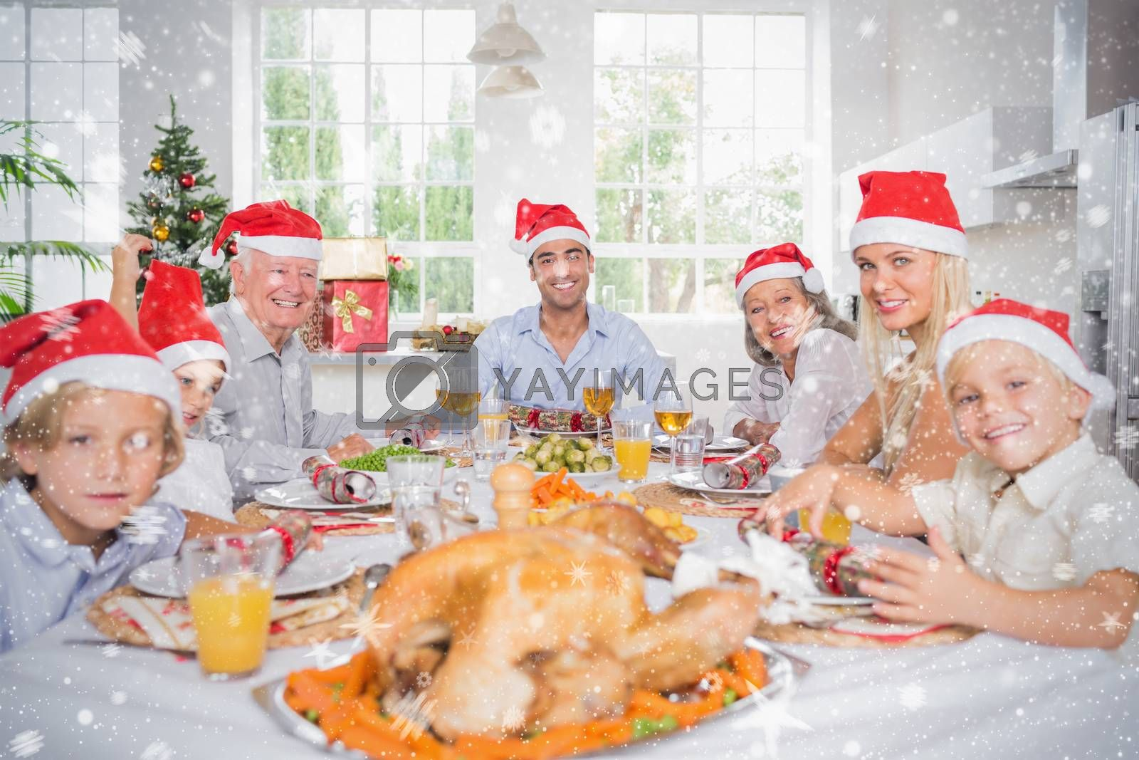 Composite image of Smiling family around the dinner table at christmas against snow
