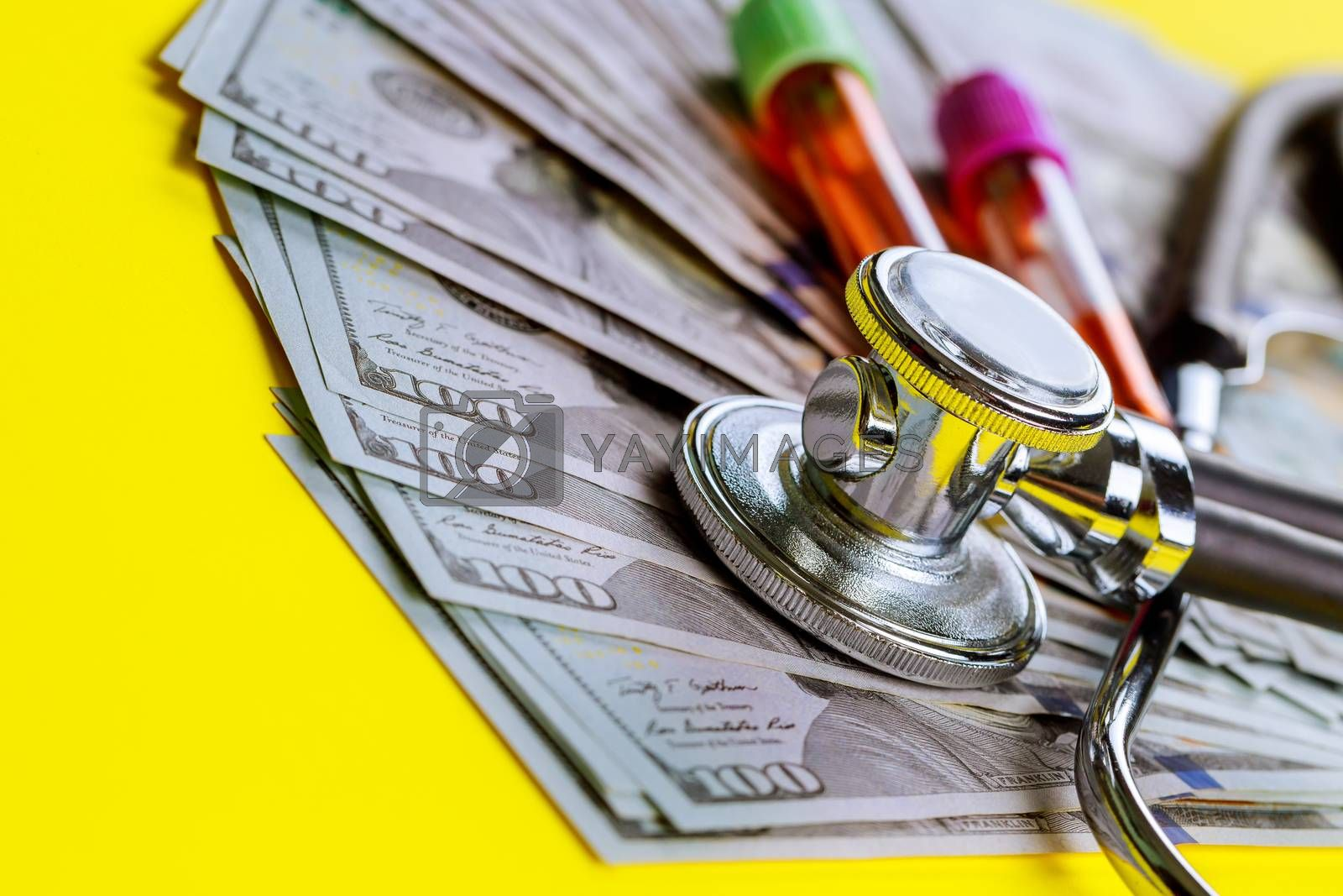 Stethoscope on of one hundred dollar bills, blood test tubes expensive cost of healthcare or financing medicine