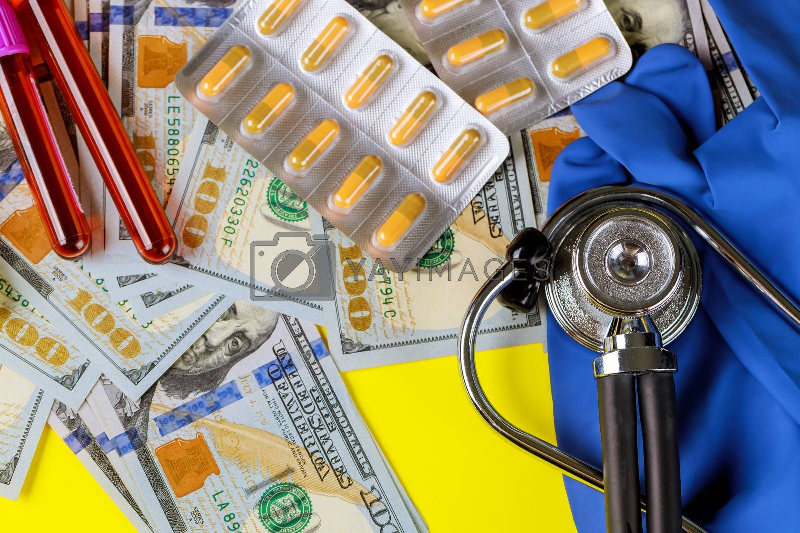 Money dollar with pills in blister on a stethoscope blood test tubes for pills blisters expensive cost of healthcare or financing medicine