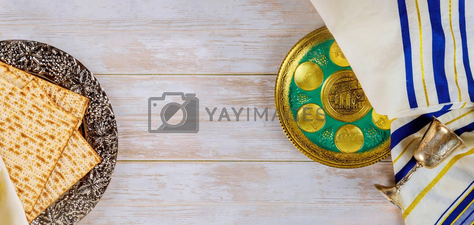 Passover jewish holiday celebration matzah, kiddush and seder with text in hebrew egg, bone, herbs, karpas, chazeret and charoset.