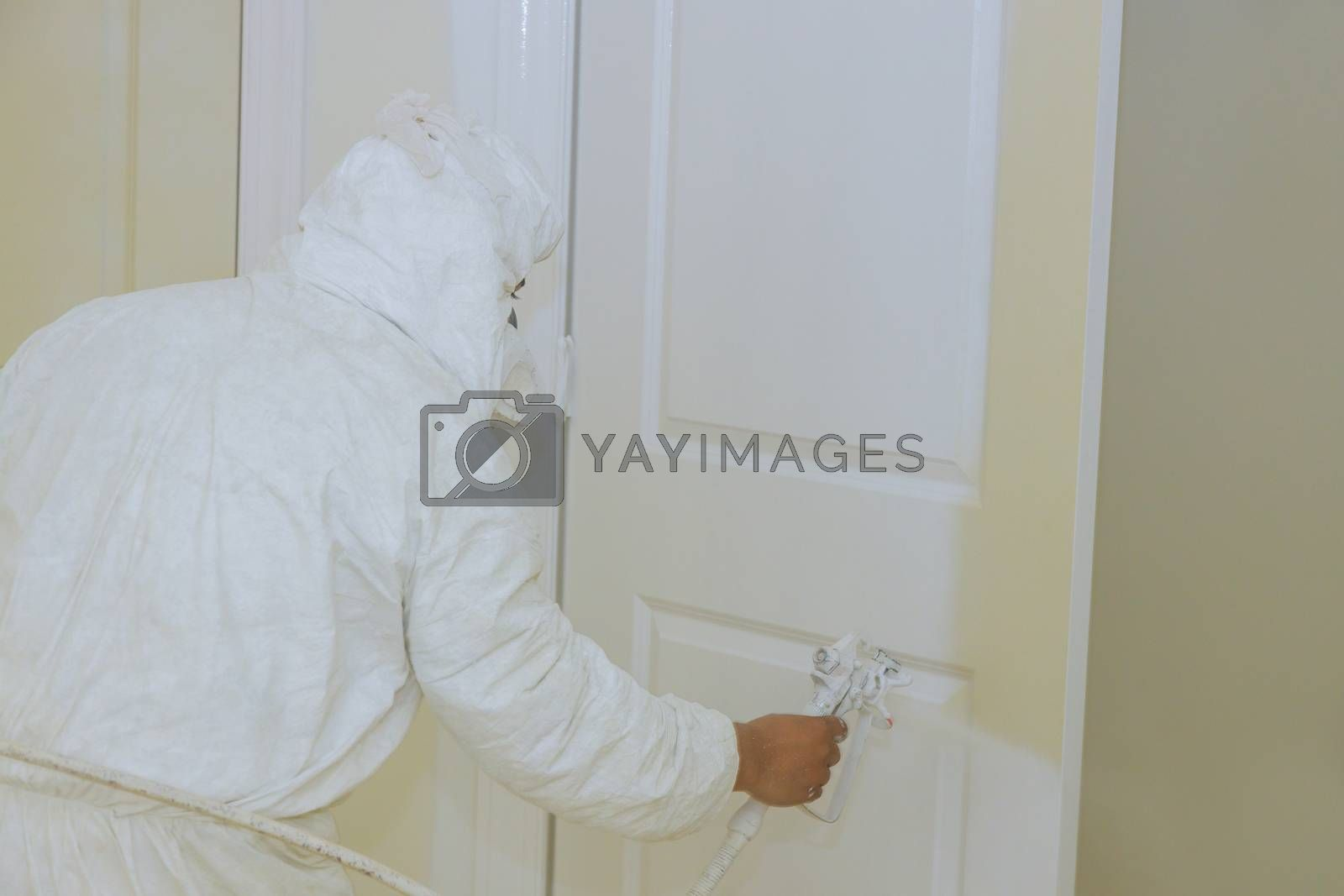 Worker painting door with spray gun in white color hand the tool the spray of paint