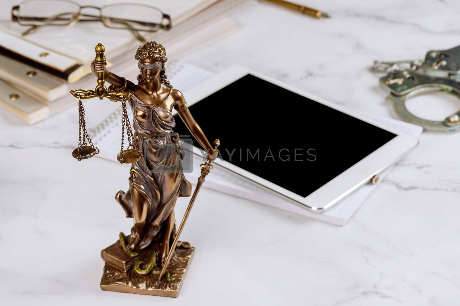 Royalty free image of Lawyer office Statue of Justice with scales and lawyer working on a digital tablet by ungvar