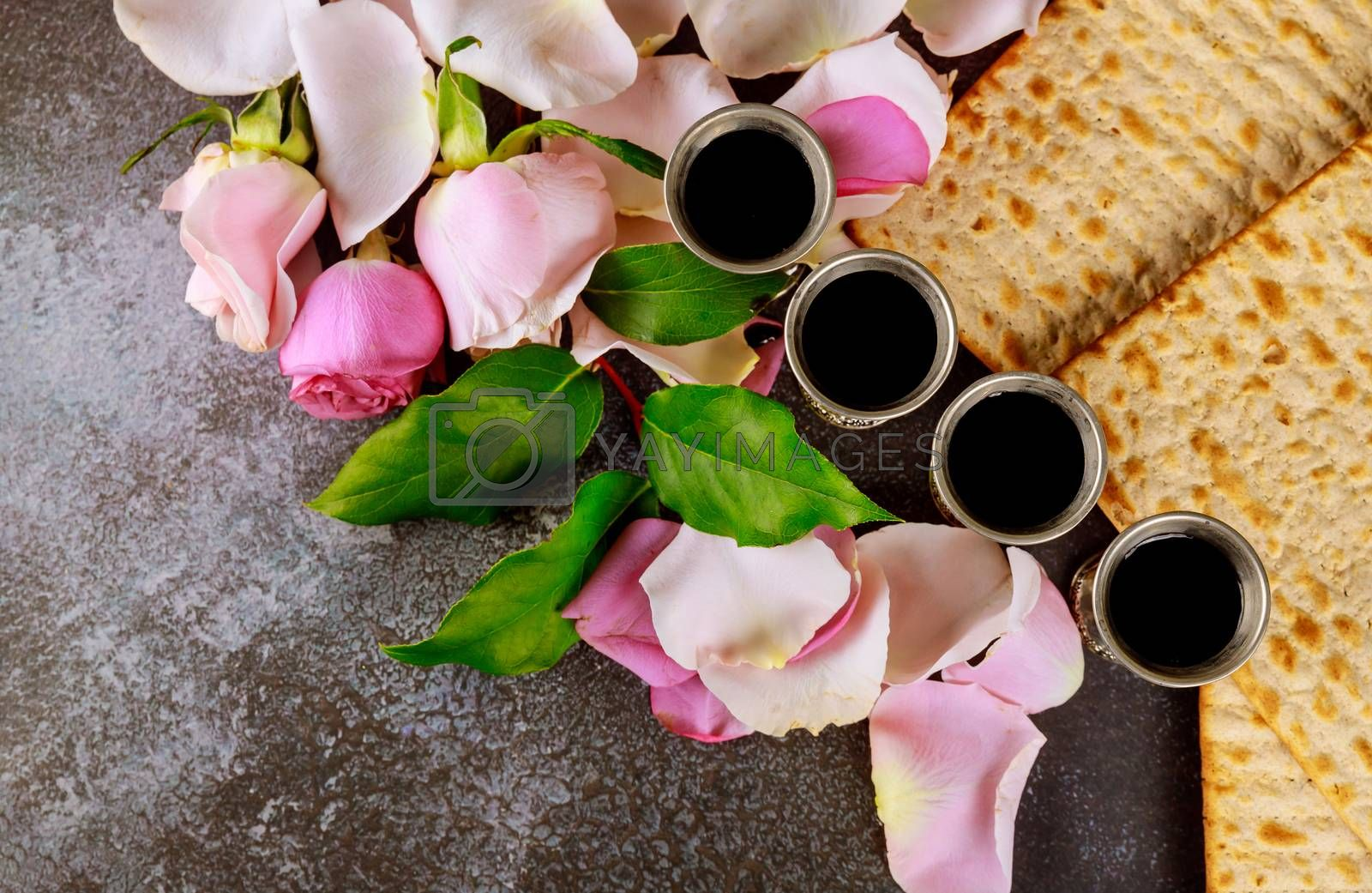 Passover celebration with matzo unleavened bread of fresh pink rose flower on kiddush cup of wine
