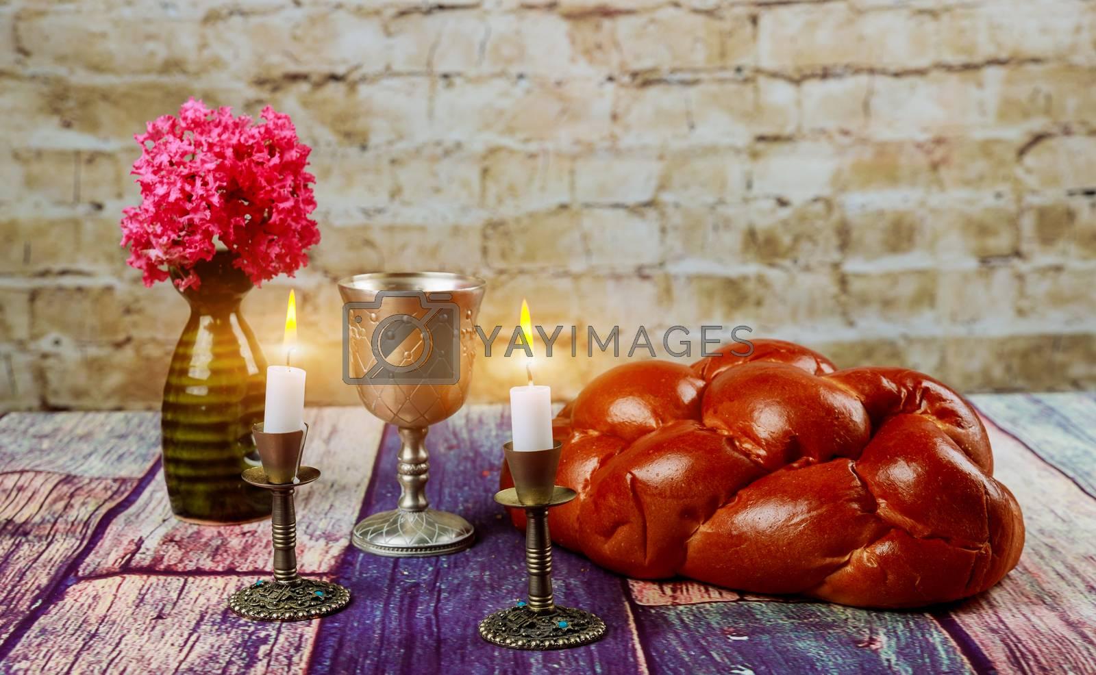 Traditional Jewish Sabbath Shalom ritual fresh challah bread with kiddush cup of red kosher wine