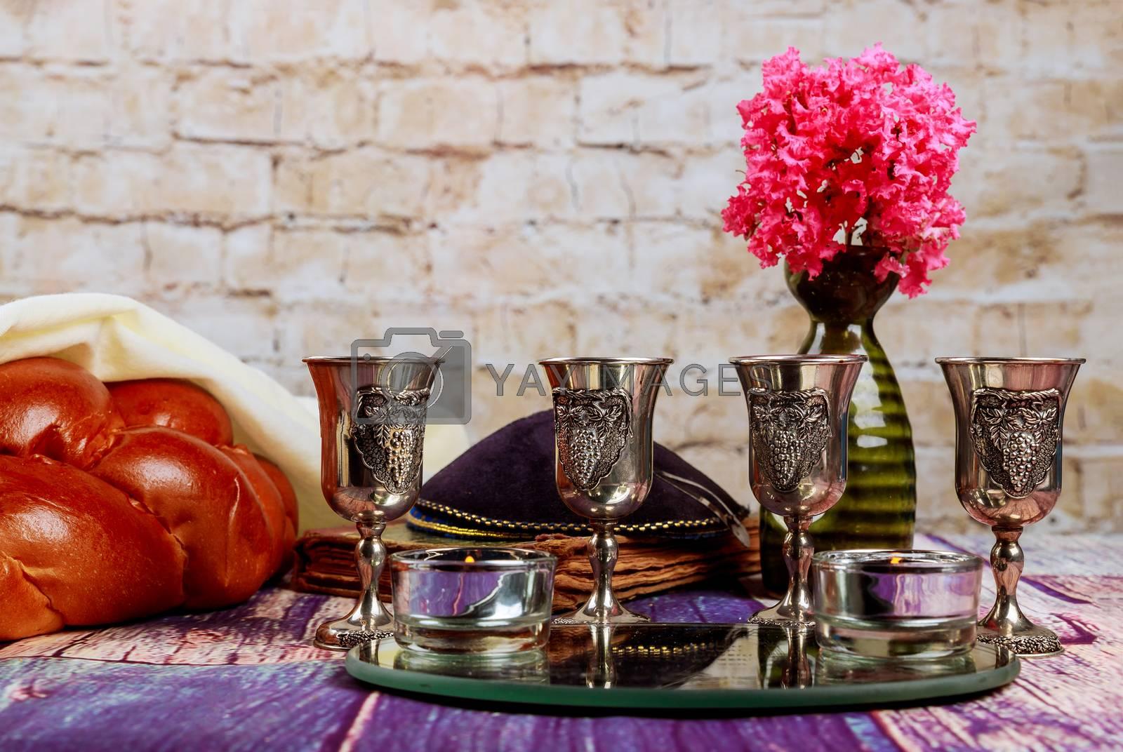 Traditional Jewish Sabbath Shalom ritual fresh challah bread with kiddush four cup of red kosher wine