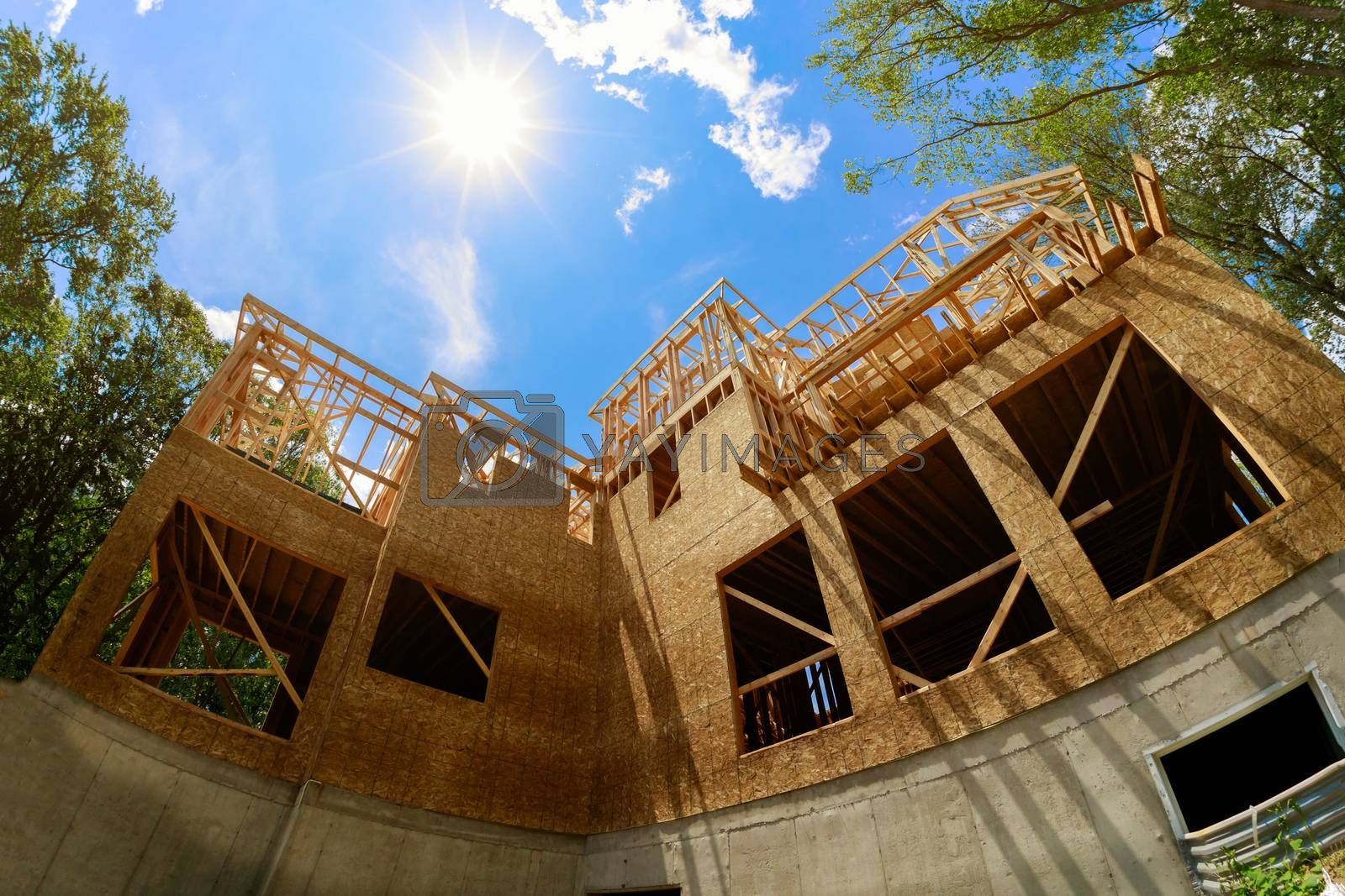 A roof on beam, built new home residential construction house framing against a blue sky