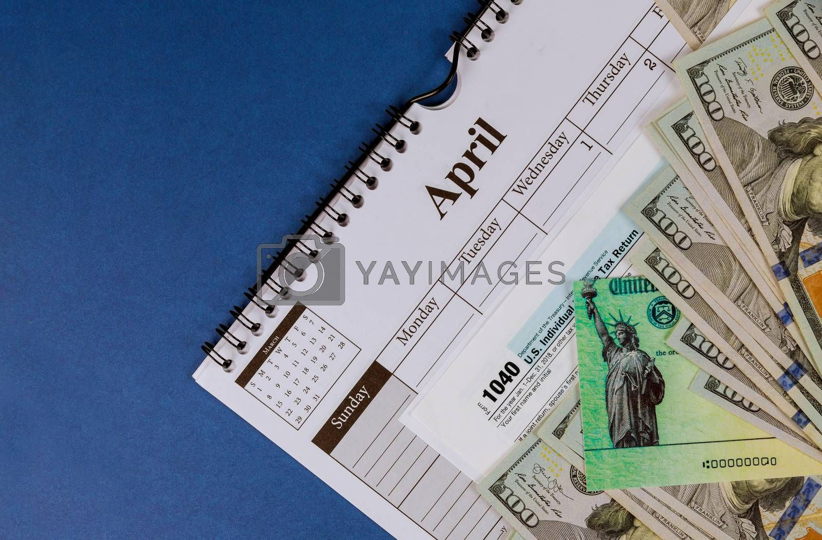 Closeup 1040 Tax form with refund check and currency US dollar banknotes