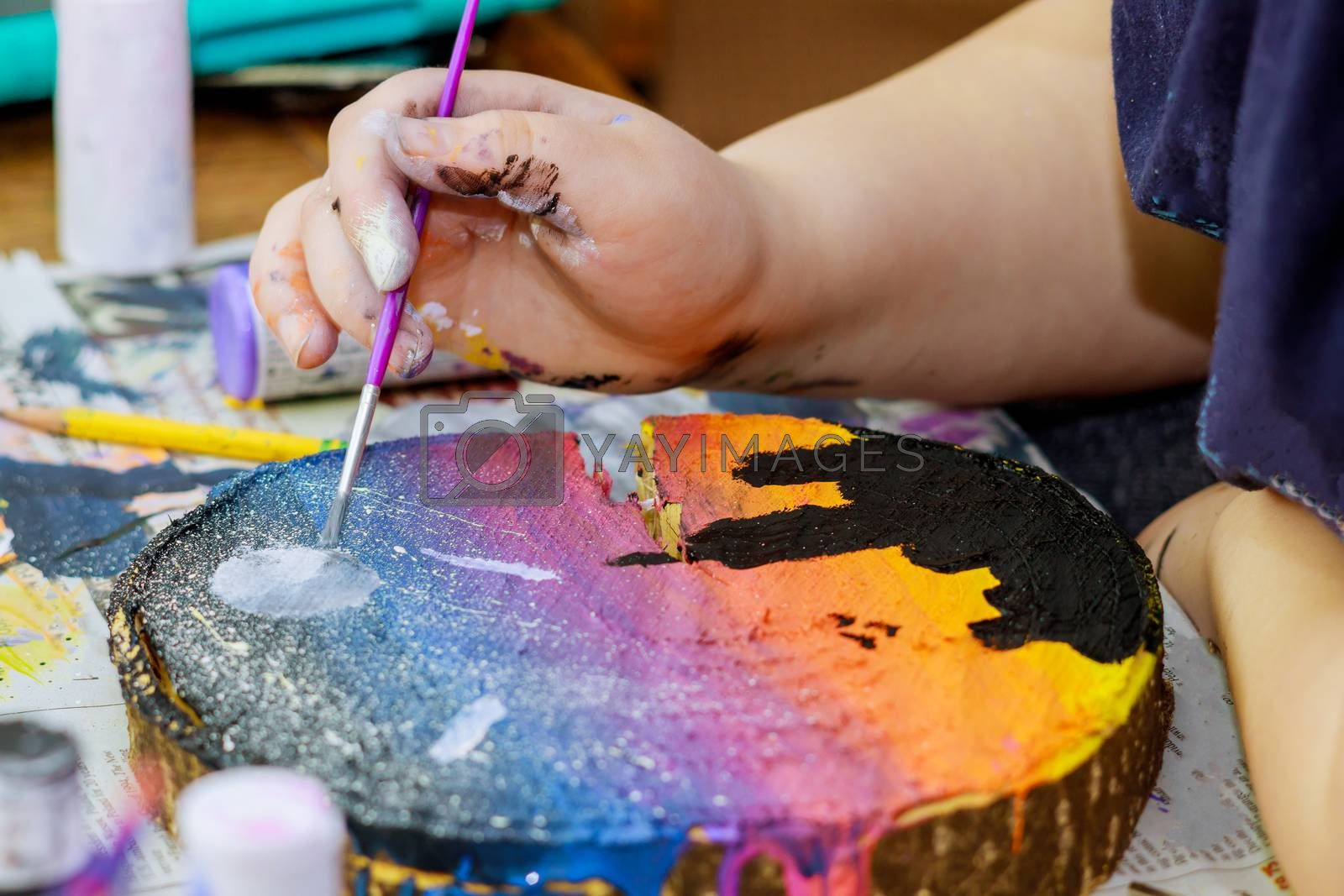 Girl draws uses colored paints brushes a picture in wooden