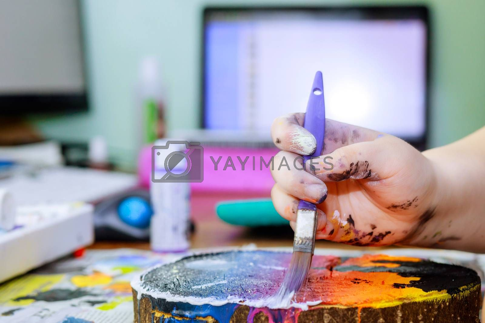 A girl uses in acrylic paint brush to make her drawings on wooden