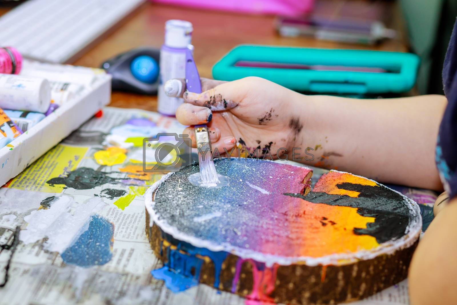 Close Up of wooden palette with acrylic paint and paintbrush in artist hands on wooden